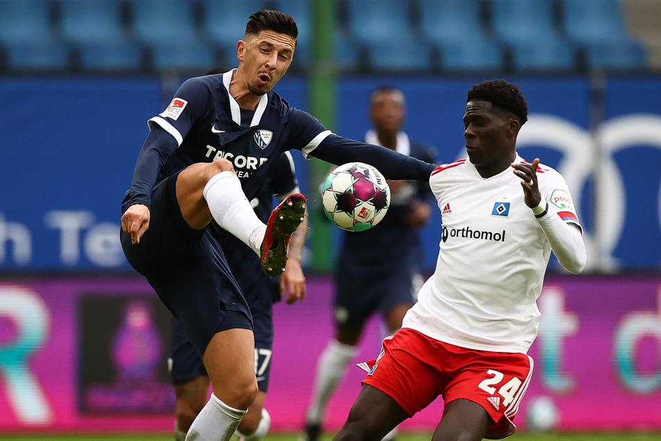 Amadou Onana (r.), Mittelfeldspieler des Hamburger SV, im Zweikampf mit Robert Zulj vom VfL Bochum.