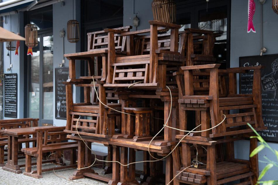 Hochgestellte Stühle und Tische stehen vor einem gastronomischen Betrieb in Mitte. Die Außengastronomie könnte womöglich bald wieder öffnen.