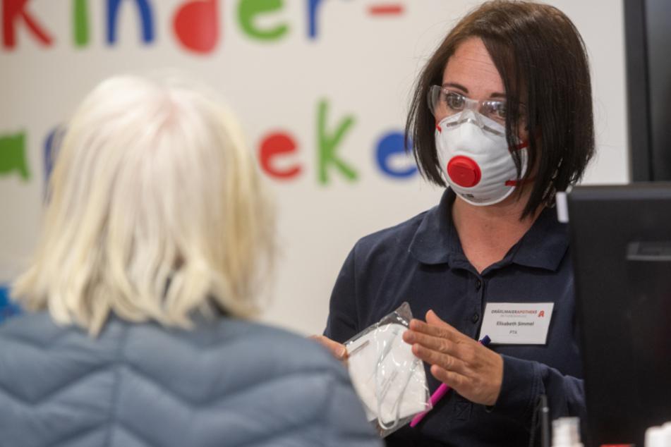 Eine Apothekenangestellte zeigt einer Kundin eine Schutzmaske.