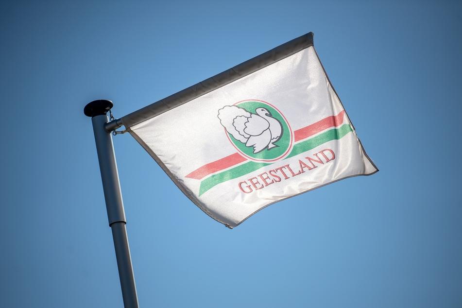 Eine Fahne mit dem Logo vom Schlachthof Geestland PutenspezialitäŠten weht im Wind.