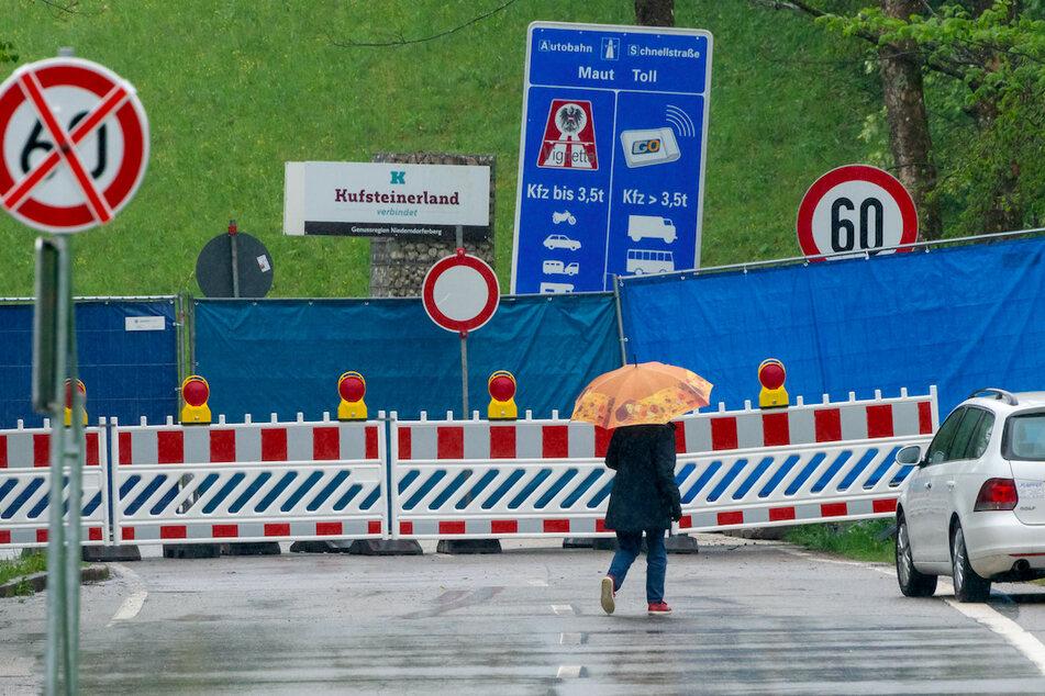 Ein Bauzaun mit blauer Sichtschutzplane trennt die deutsche Seite des Aschauer Ortsteils Sachrang auf bayerischer Seite vom Ort Niederndorferberg im Kufsteinerland in Tirol (Österreich).