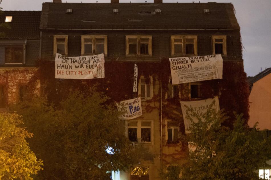 Transparente von Aktivisten hängen an den Fenstern eines leerstehenden Wohnhaus. Mit der Hausbesetzung wollen die Aktivisten eigenen Angaben zufolge gegen steigende Mieten, Zwangsräumungen und Profitinteressen von Immobilienfirmen protestieren.