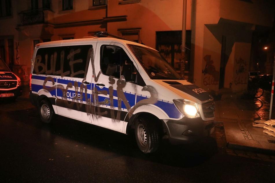 """Auf der Beifahrerseite des Polizeiwagens steht der Schriftzug """"Bullen Schwein""""."""