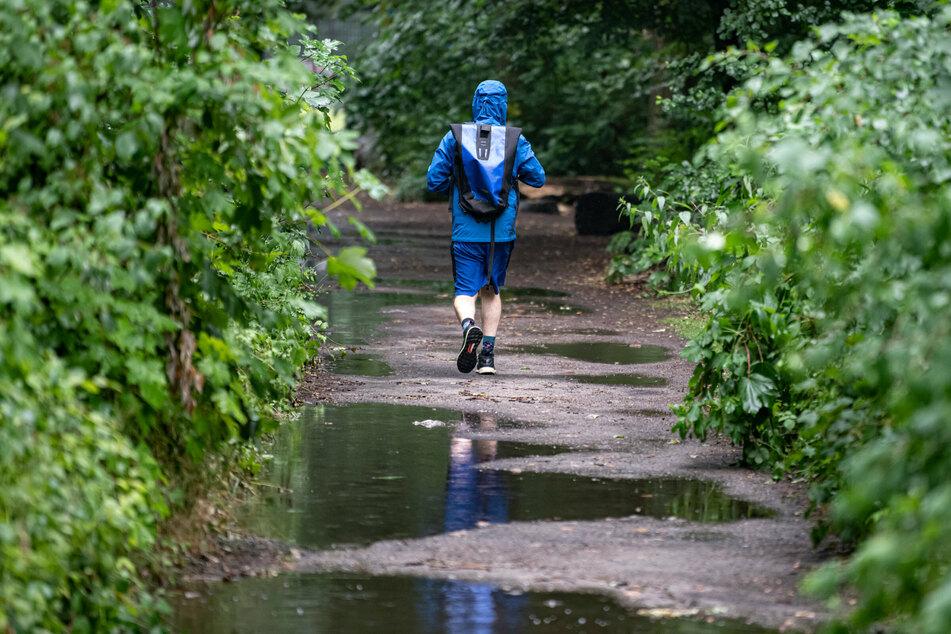 Eine Person geht durch den verregneten Plänterwald. Auch in Berlin wird es am Sonntagabend wieder nass.
