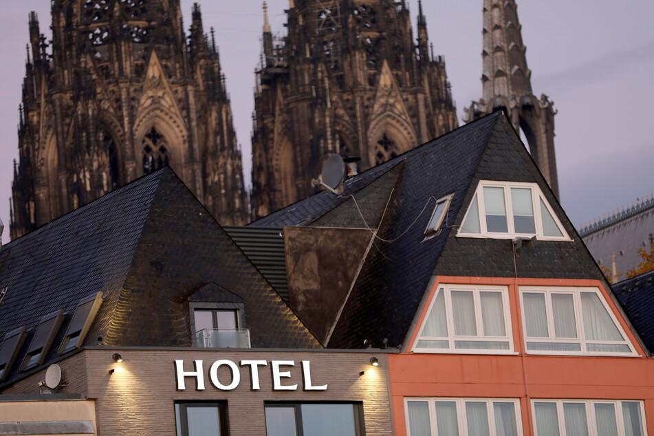Ein Schriftzug leuchtet am Morgen an einem Hotel in der Nähe des Kölner Domes.