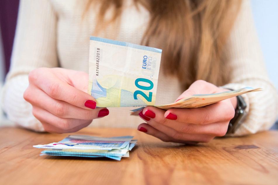 Eine Frau hält Geldscheine in der Hand. In der Corona-Krise haben viele Menschen deutlich mehr gespart. (Symbolbild)
