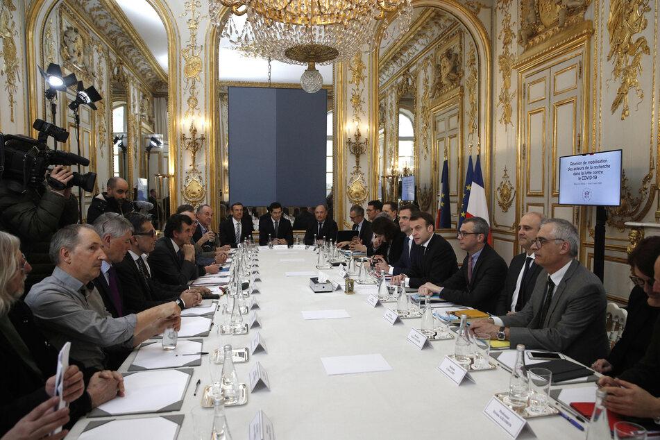 Der französische Präsident Emmanuel Macron (4.v.r) und der Gesundheitsminister Olivier Veran (5.v.r) empfangen angesichts der Coronavirus-Epidemie Wissenschaftler, Forscher und Experten zu einem Arbeitstreffen im Élyséepalast.