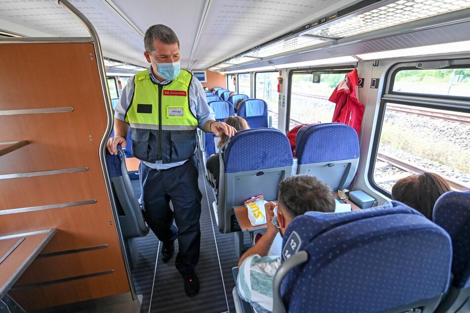 Leipzig: Lutz Fuge (l) vom Präventionsteam der Deutschen Bahn kontrolliert in einem Intercity zwischen Leipzig und Halle das Tragen von Mund-Nasen-Bedeckungen bei den Fahrgästen. Der Großteil der Passagiere reist mit Mund-Nasen-Schutz, Fahrgäste ohne Maske, werden vom Team der Bahn gebeten, die Bedeckung zu tragen, soweit kein Attest vorliegt.