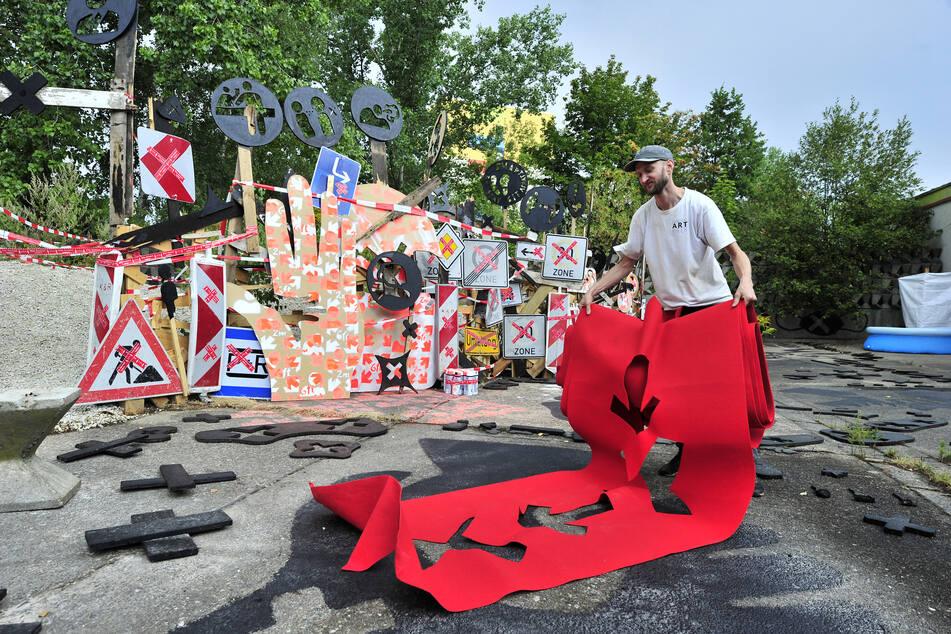 Christoph Mügge (36) bereitet sein Kunstwerk aus Schildern, Absperrungen und Piktogrammen vor.