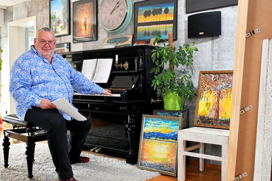 Andreas Goldmann (56) ist beim Komponieren am Klavier von seinen eigenen Bildern umgeben.
