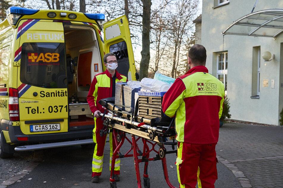 Die Chemnitzer ASB-Mitarbeiter Ben Fleischer (l.) und Christian Homburg transportieren 145 gekühlte Anti-Corona-Impfdosen auf einer Trage zu einem Altenheim.