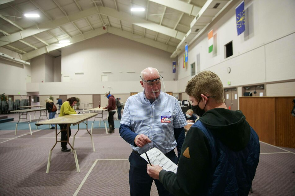 A poll worker helps a voter with information about how to cast a ballot at the Southside Christian Church in Bloomington, Indiana.