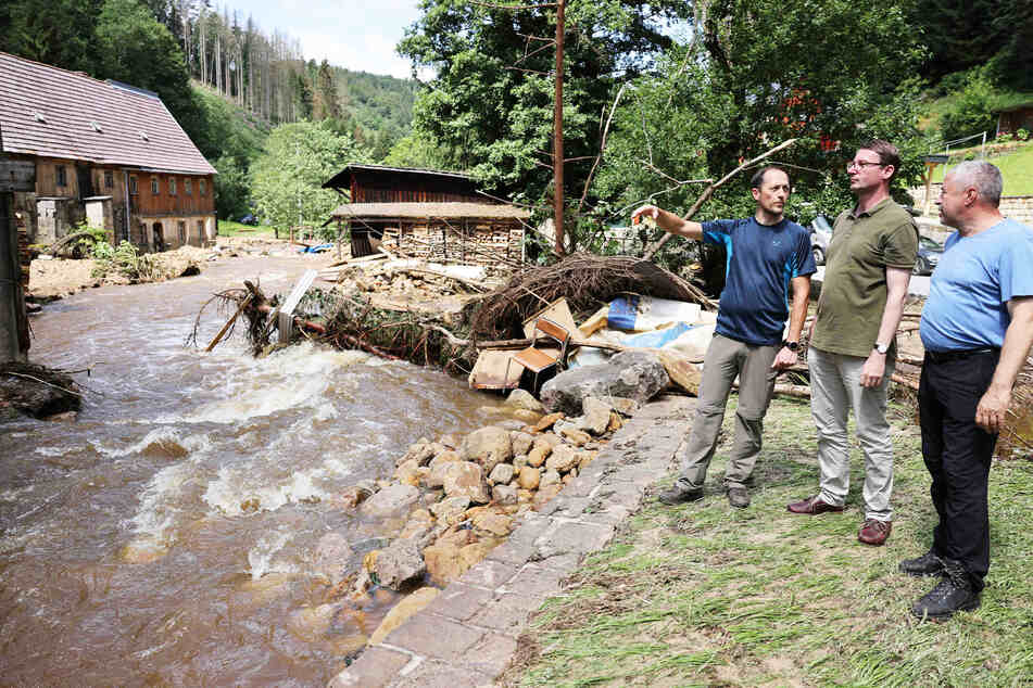 Thomas Kunack (43, WV Tourismus, v.l.n.r.), Bürgermeister von Bad Schandau, Innenminister Roland Wöller (50, CDU) und Michael Geisler (61, CDU), Landrat Sächsische Schweiz-Osterzgebirge, schauen sich in Krippen die Schäden nach dem Hochwasser an.