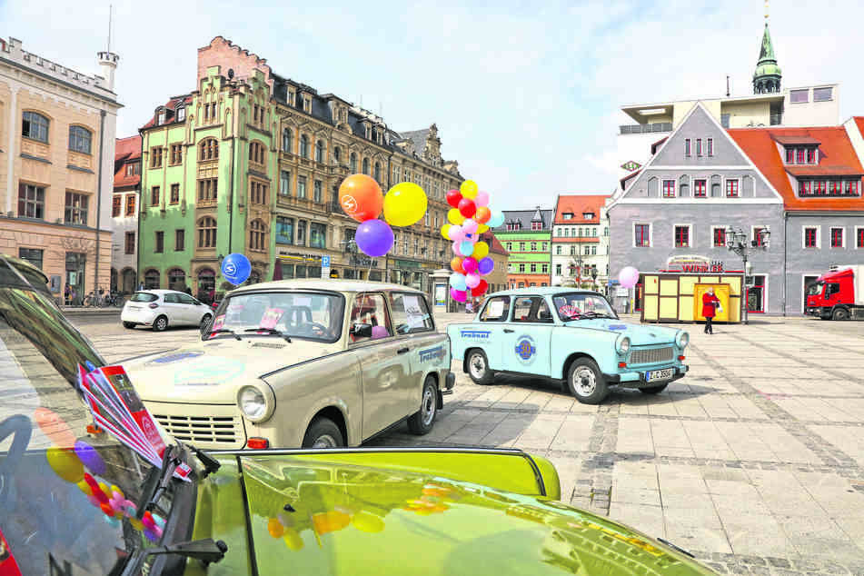 """Die """"Pappe"""" ist Kult: Drei mit Luftballons geschmückte Trabis standen am Freitag zum stummen Gedenken auf dem Zwickauer Hauptmarkt - zwei Limousinen (caprigrün und gletscherblau) sowie ein papyrusweißer 1.1 Kombi aus dem Besitz des Vereins Inter Trab."""