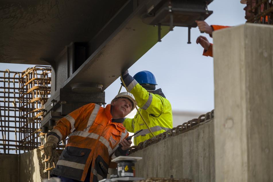 Strabag-Mitarbeiter setzen einen 100 Tonnen schweren Stahlträger passgenau auf Beton-Widerlager.