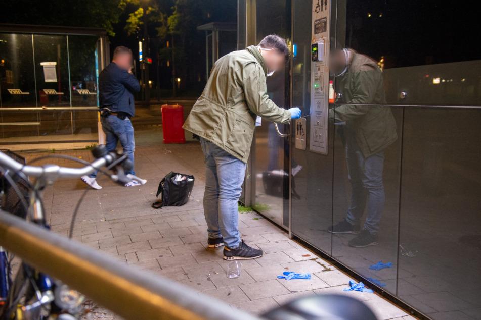 Ein Ermittler sichert Spuren am Tatort an einem WC-Häuschen.