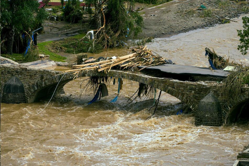 Die Wassermassen der Ahr fließen unter einer Brücke im Ort Schuld hindurch.