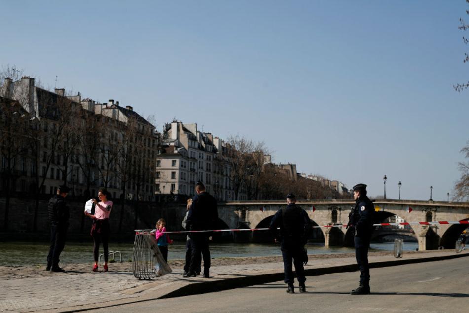 Paris:Französische Polizeibeamte kontrollieren eine an der Seine joggende Frau.