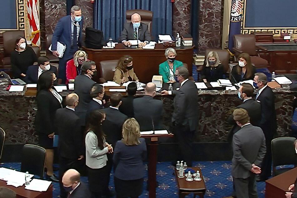 Die Beteiligten sprechen miteinander während der Fortsetzung des zweiten Amtsenthebungsverfahrens gegen den früheren US-Präsidenten Trump im US-Senat.