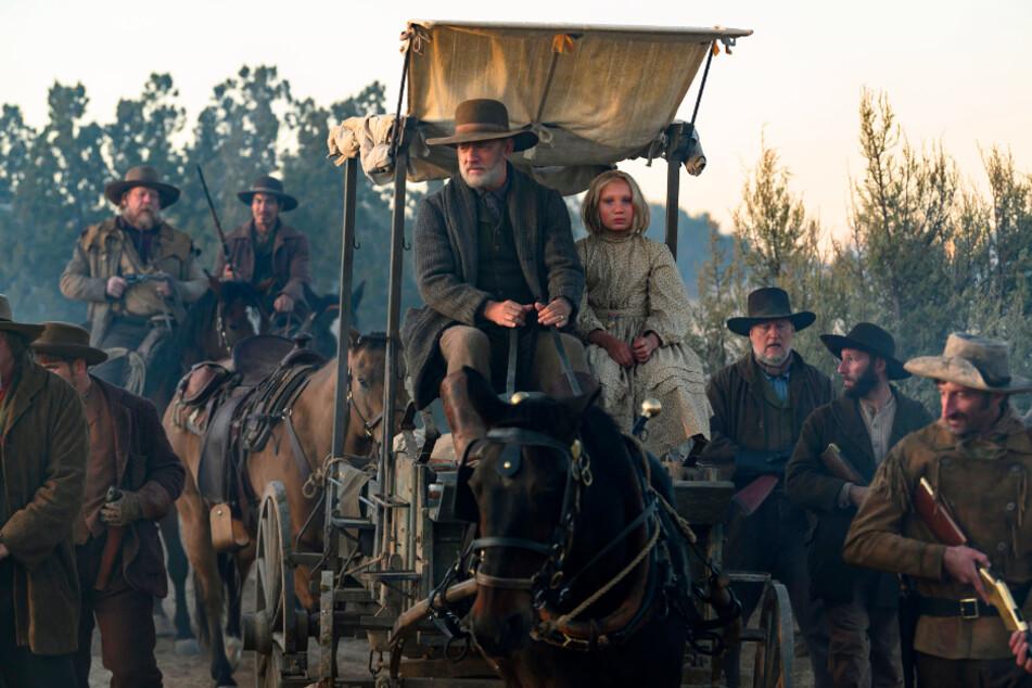 Bürgerkriegs-Veteran Jefferson Kyle Kidd (Tom Hanks) und Johanna Leonberger (Helena Zengel, beide auf dem Kutschbock) treten gemeinsam eine harte Reise durch den Wilden Westen an.