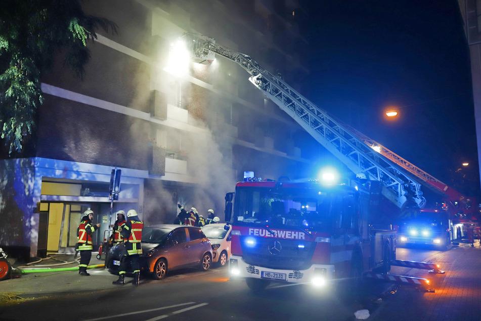 Feuerwehrleute löschen den Brand in dem mehrstöckigen Haus und evakuieren über die Drehleiter Bewohner aus höher gelegenen Wohnungen.
