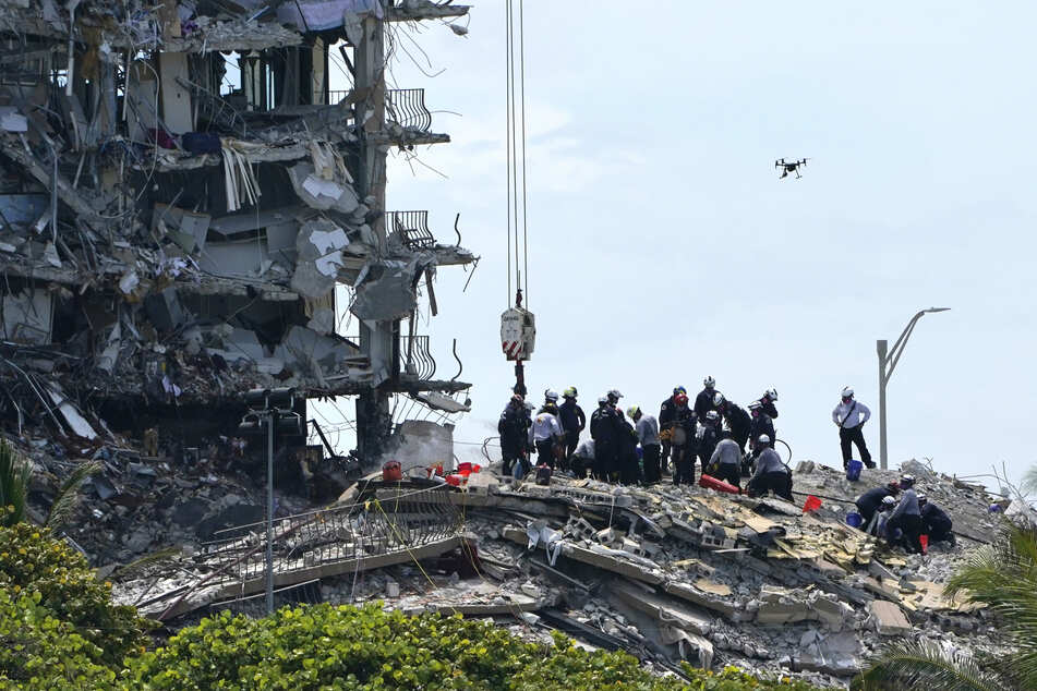 Such- und Rettungskräfte bei den Trümmern im teilweise eingestürzten Gebäude.