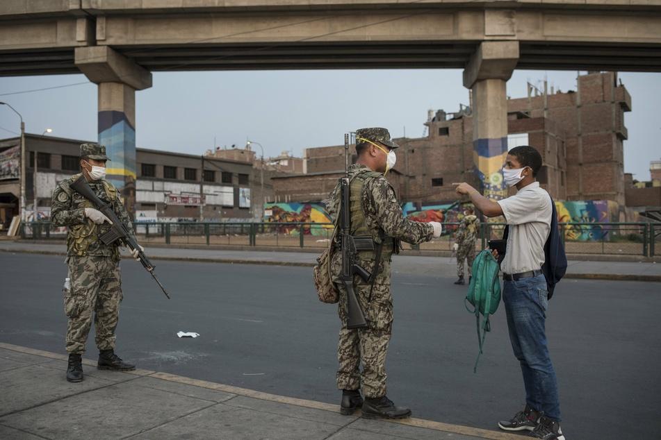 Soldaten überprüfen während einer Ausgangssperre, die die Ausbreitung des neuartigen Coronavirus verlangsamen soll, die Dokumente eines Mannes.