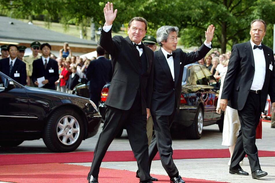 Der damalige Bundeskanzler Gerhard Schröder (SPD) und der damalige japanische Ministerpräsident Junichiro Koizumi winken bei ihrer Ankunft zu den Richard-Wagner-Festspielen im Jahr 2003 in Bayreuth. (Archiv)