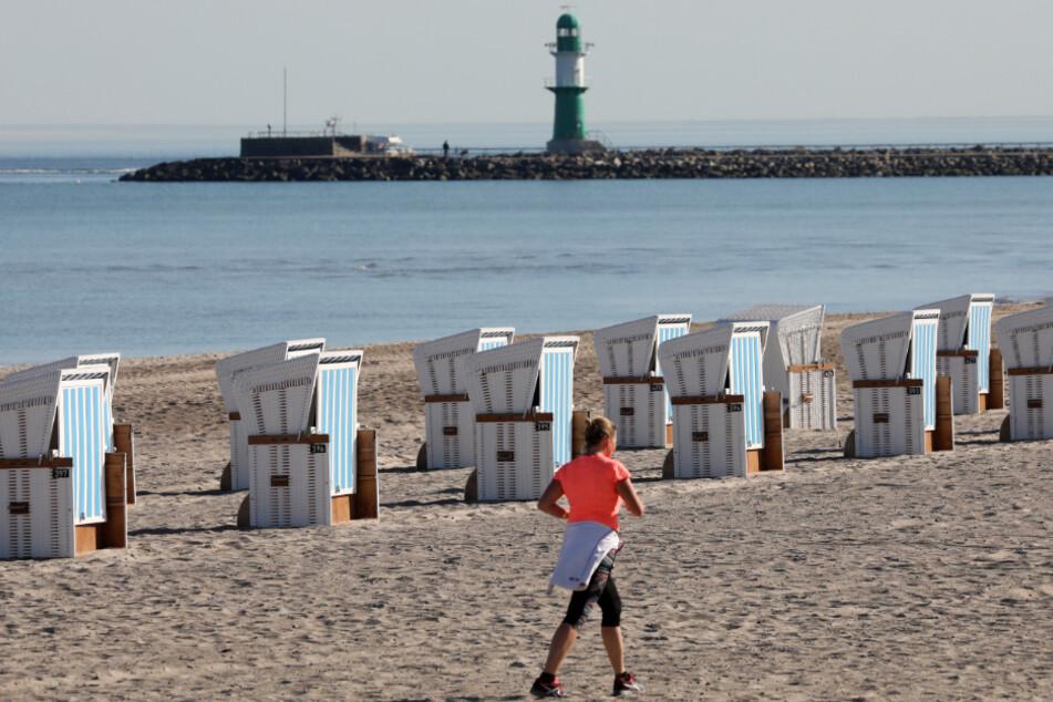 Eine Joggerin sportelt am Strand. Um sie herum stehen Strandkörbe bereit (Symbolbild).
