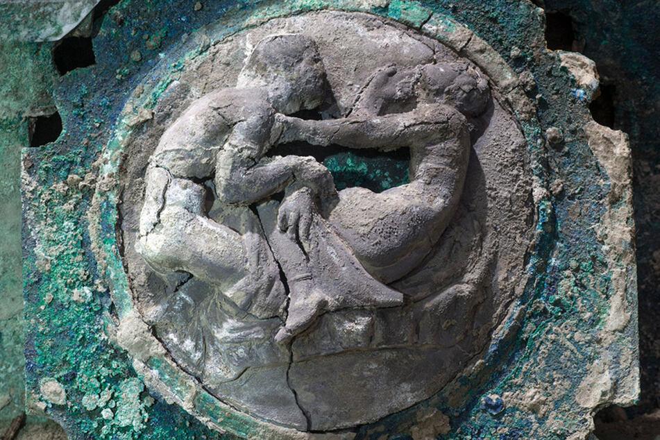 Auf der Seite des Triumphwagens sieht man erotische Motive mit nackten Männern und Frauen.