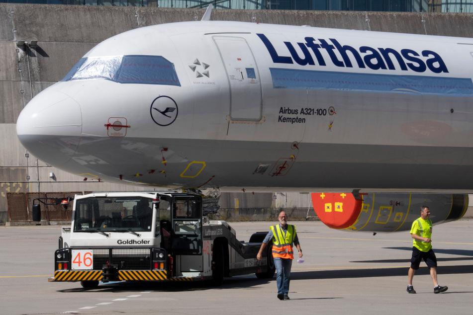 Eine Passagiermaschine der Lufthansa wird zum Technik-Hangar der Airline auf dem Flughafen Frankfurt geschleppt. Dabei sind die Fenster und Triebwerke der Maschine nach monatelangem, corona-bedingtem Stillstand zum Schutz vor Umwelteinflüssen abgeklebt.