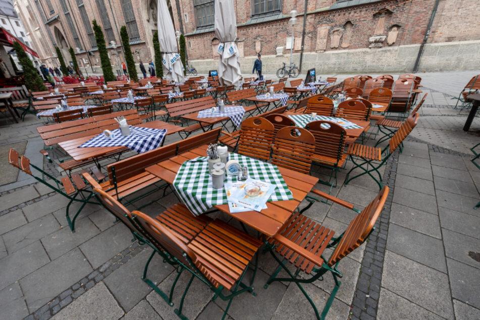 Leere gedeckte Tische stehen um die Mittagszeit vor einem Restaurant nahe der Frauenkirche (im Hintergrund) vor einem Restaurant.