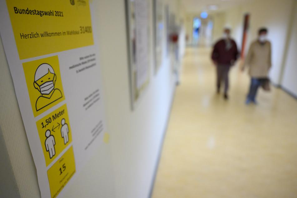 Ein Zettel mit Hygienehinweisen klebt zur Bundestagswahl in einem Wahllokal an der Wand. Bei bestem Spätsommerwetter und in der Corona-Pandemie strömten die Menschen in Sachsen nicht gerade in die Wahllokale.