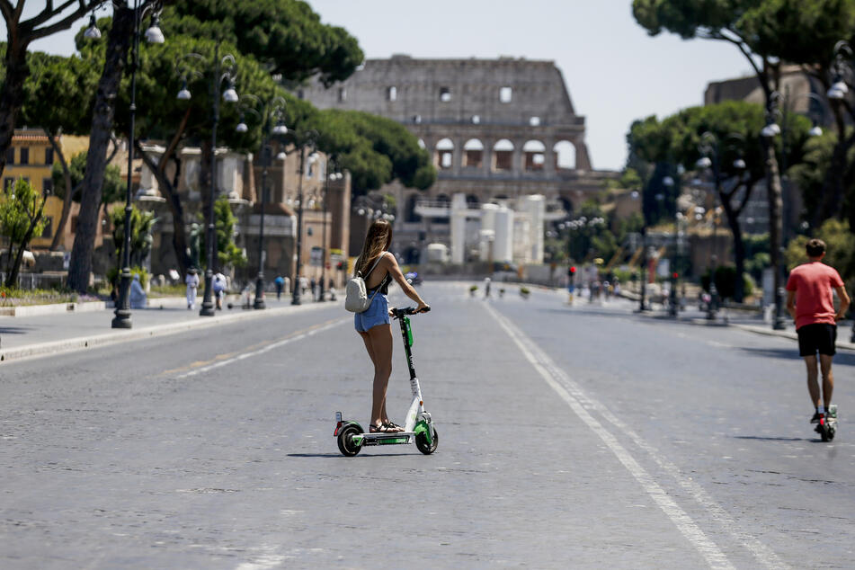 Rom: Touristen fahren mir E-Rollern auf das Kolosseum zu.