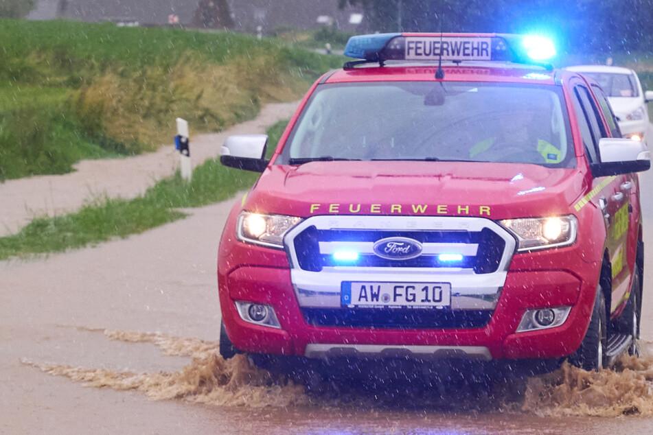 Ein Feuerwehrauto fährt bei Gelsdorf über eine überflutete Landstraße: Nach starken Regenfällen und Überschwemmungen herrscht an vielen Orten in Rheinland-Pfalz Land unter.