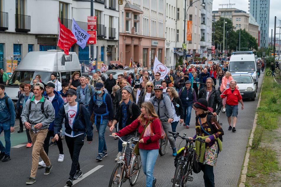 Aus Protest gegen die Corona-Politik wandern Demonstranten durch eine Straße.