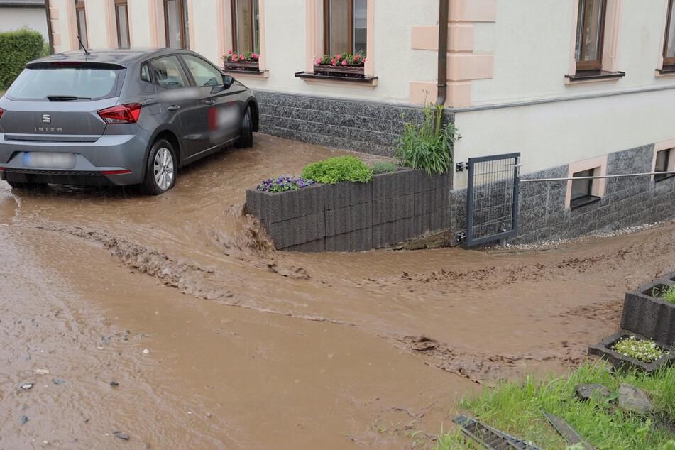 Die Straßen verwandelten sich teilweise in reißende Flüsse - hier schießen die Wassermassen in ein Grundstück.