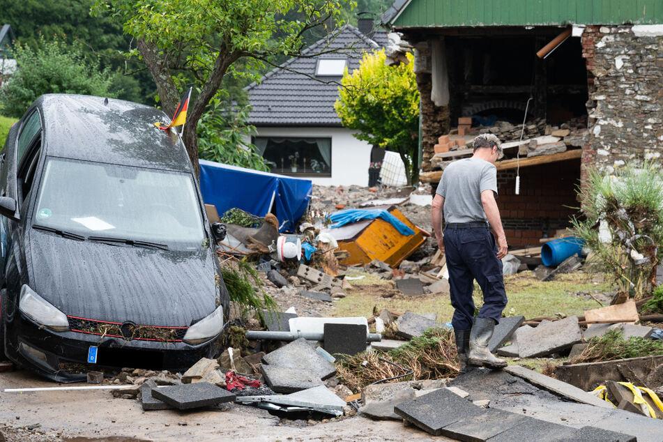 Ein Anwohner steht zwischen den Trümmern der Unwetterschäden im Ortsteil Hohenlimburg in Hagen.