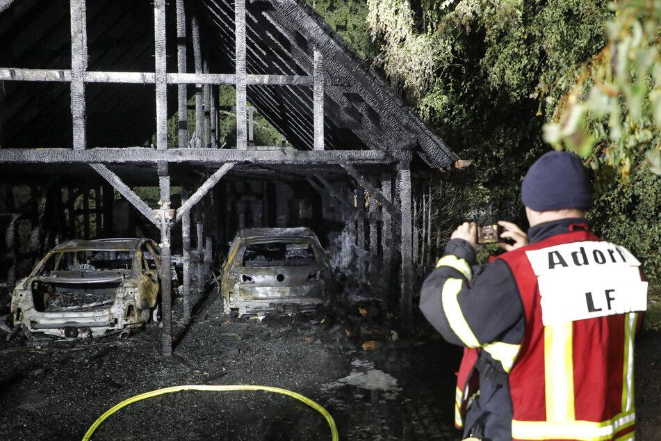 In Neukirchen schießt ein Feuerwehrkamerad aus Adorf ein Beweisfoto vom Doppelgaragen-Brand.