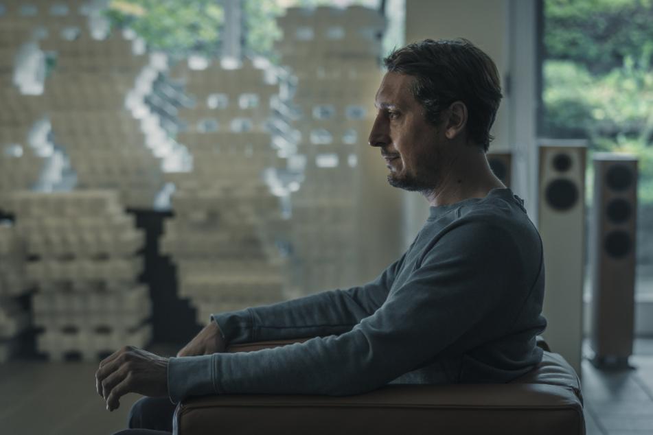 Martin Schellenberg (Hans Löw) sitzt nachdenklich in seiner Boxenwerkstatt.