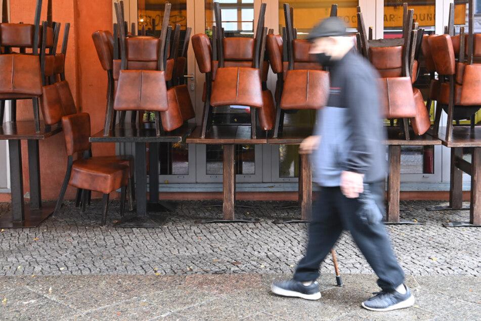 Ein Mann mit Mundschutz geht an einem geschlossenen Restaurant vorbei.