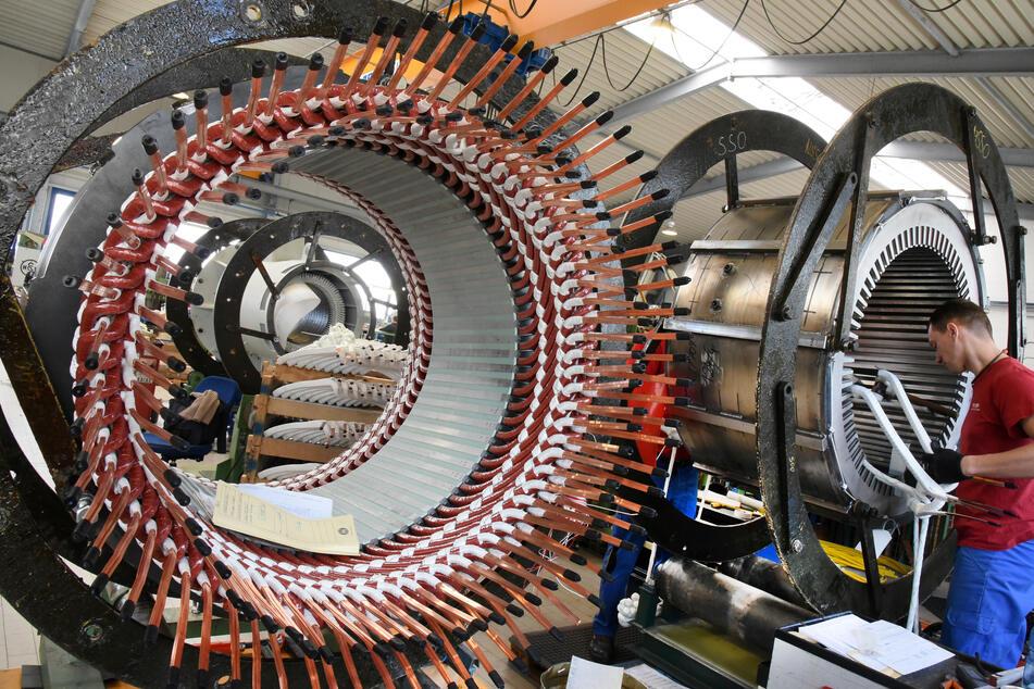 In einem Reparaturwerk arbeitet ein Mitarbeiter an Statoren für Elektromotoren und Generatoren.