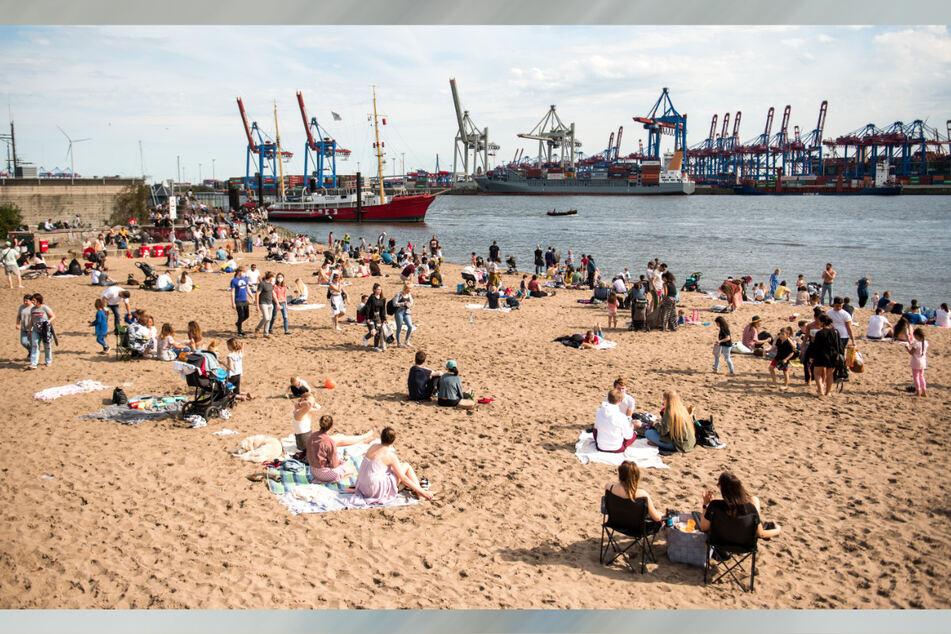 Zahlreiche Menschen waren am Sonntag bei Sonnenschein am Elbstrand in Övelgönne unterwegs. In Hamburg liegt die Sieben-Tage-Inzidenz am Montag den fünften Werktag in Folge unter 100.