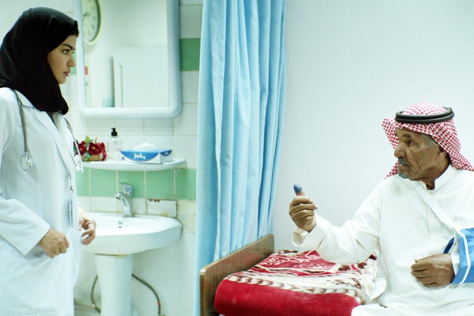 Maryam (Mila Alzahrani) möchte Abu Musa (Hamad Almuzainy) helfen, der aber auf keinen Fall will, dass eine Frau ihn behandelt.