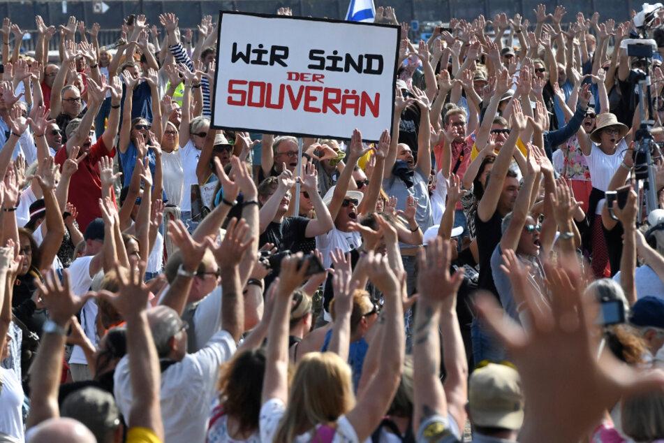 Düsseldorf: Teilnehmer einer Demonstration protestieren mit Schildern auf den Rheinwiesen gegen die Maßnahmen zur Bekämpfung des Coronavirus.