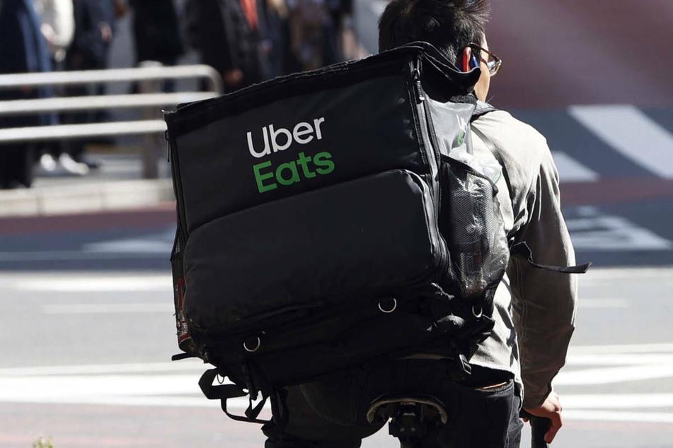 Ein Mitarbeiter des Essenslieferdienstes Uber Eats radelt mit einer Lieferung durch Tokio. Der Lieferservice plant in einigen Wochen den Einstieg in den deutschen Markt, beginnend in Berlin.
