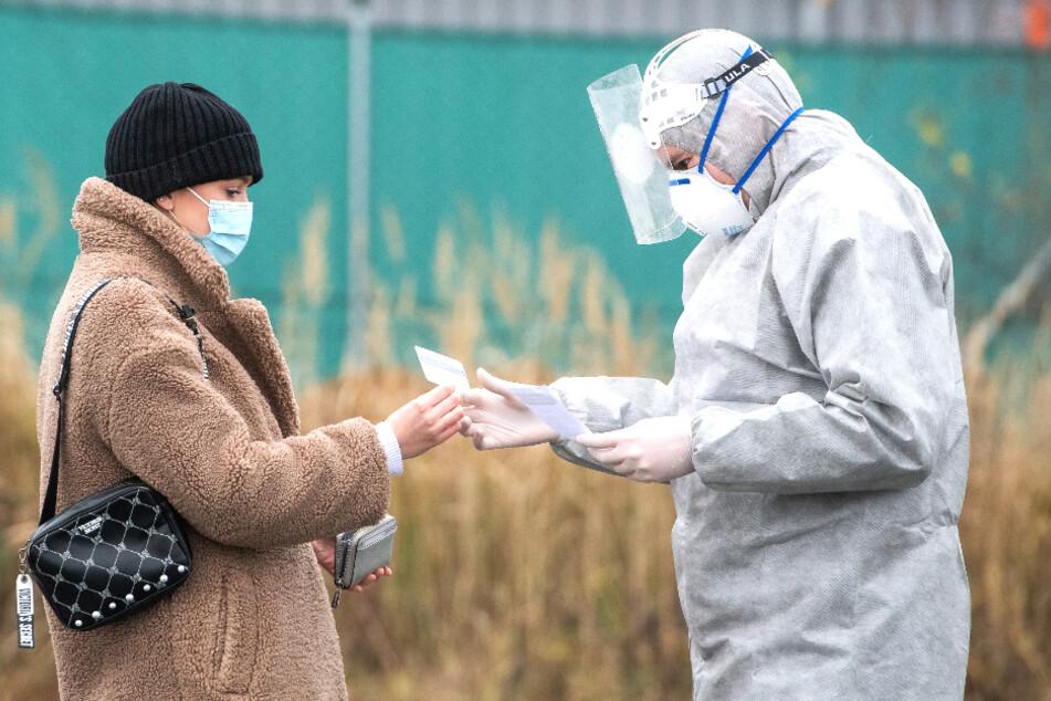 Pilsen: Ein Mitarbeiter des Gesundheitswesen trägt Schutzkleidung und schaut sich an einer Corona-Teststation Papiere einer Frau an.