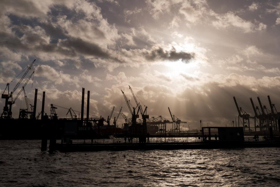 Durch dunkle Regenwolken scheint etwas Sonne über den Hafenanlagen in Hamburg. (Symbolfoto)