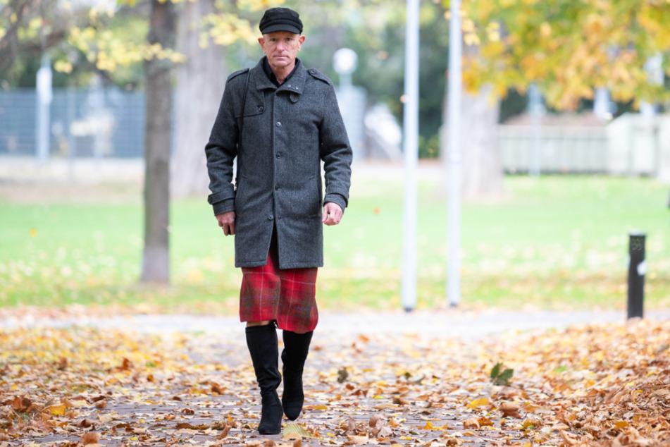 Mark Bryan, Influencer auf Instagram, geht unter einem Baum entlang. Er trägt gerne High Heels und zieht damit jede Menge Blicke auf sich.