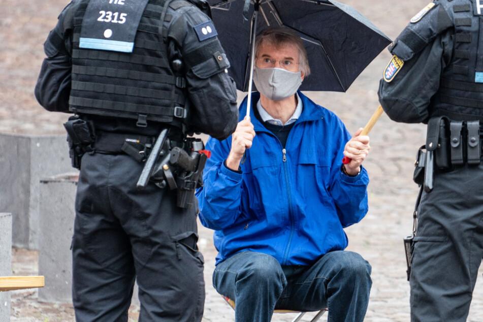 Ein Friedensaktivist wird von Polizisten aufgrund des Versammlungsverbotes vom Römerberg in Frankfurt weggeschickt.